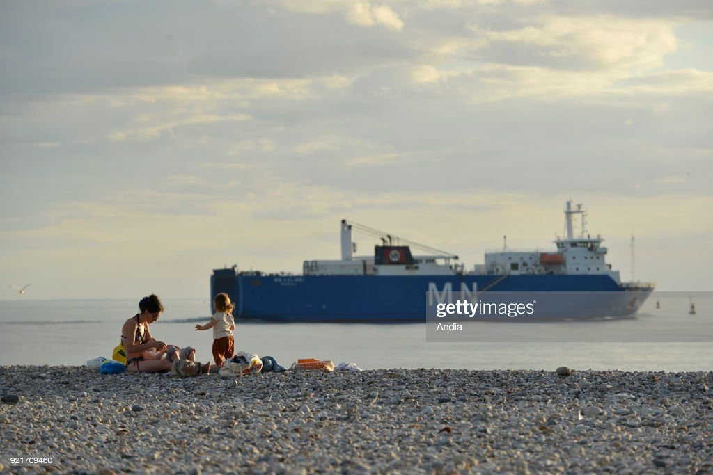 Le Havre (Normandy region, north western France): woman and her child on the pebble beach and container ship off the coast sailing back to the port.
