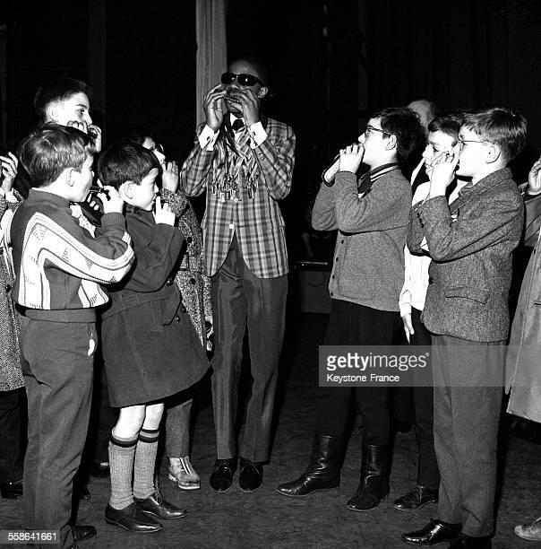 Le jeune musicien et chanteur Stevie Wonder a reçu un harmonica en or de la part de 20 jeunes garçons parisiens représentant chacun un arrondissement...