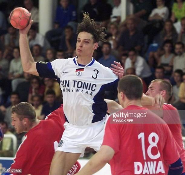 le joueur allemand Frank Van Behren tire au but entre les défenseurs russes Edouard Kokgharov et Viatschleslav Gorpichine le 30 août 2000 à...