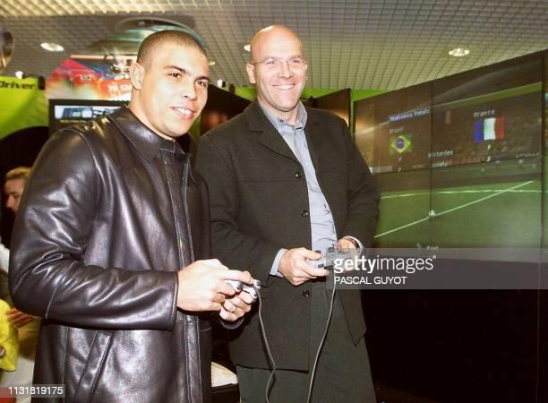 Le joueur de football brésilien Ronaldo fait une démonstration d'un jeu vidéo portant son nom avec Bruno Bonnell, le PDG d'infogrames, le 17 février...