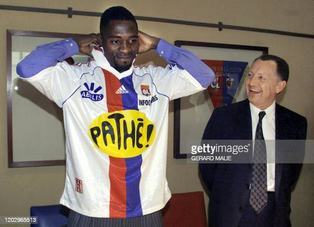 Le joueur de football Marc-Vivien Foe , milieu de terrain international camerounais, ajuste son nouveau maillot sous le regard du président de...