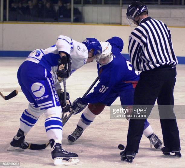 le joueur de l'équipe de France de hockey Richard Aimonetto dispute le palet avec le joueur finlandais Mikka Lindholm le 27 décembre 2001 à la...