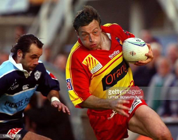 le joueur de Perpignan Dan Luger s'échappe avec le ballon avant de marquer un essai malgré le joueur de Castres Ugo Mola le 14 mai 2004 lors de leur...