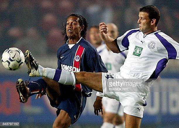le joueur du Paris SaintGermain le Brésilien Ronaldinho est à la lutte avec le défenseur hongrois Zoltan Szeles le 19 septembre 2002 au Parc des...