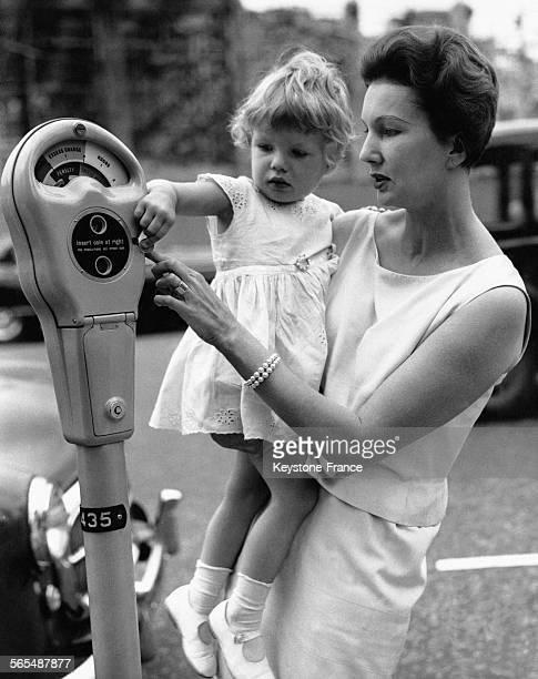 Le mannequin Barbara Goalen tenant dans ses bras sa fille Emma mettant une pièce de monnaie dans le parcmètre à Mayfair Londres RoyaumeUni le 10...
