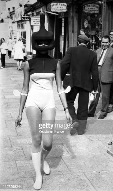 Le mannequin Valerie SaintHelen présente un ensemble de bain vert et bleuroi avec un casque spatial et des chaussettes vert pistache dans les rues de...