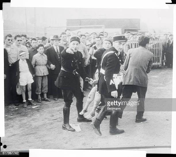After Racing Accident One of the policemen carrying away the body of a woman killed in the Le Mans auto racing tragedy stops to yell at the...