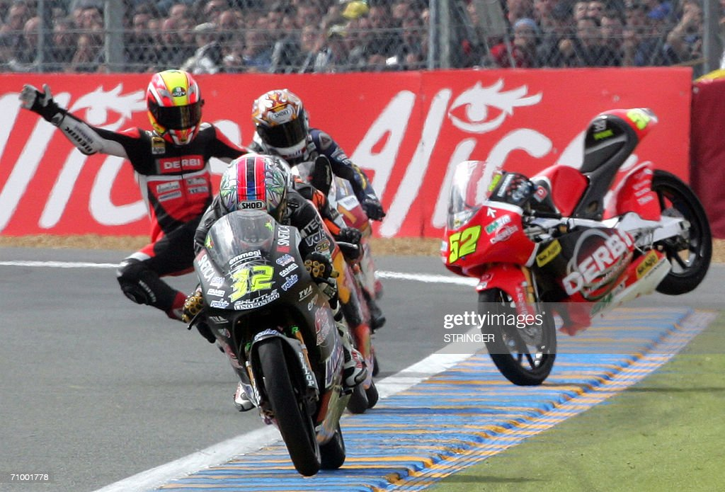 Czech Lukas Pesek (L) falls down during the 125cc race during the French 125cc Grand Prix , 21 May 2006 at the Le Mans racetrack, western France.