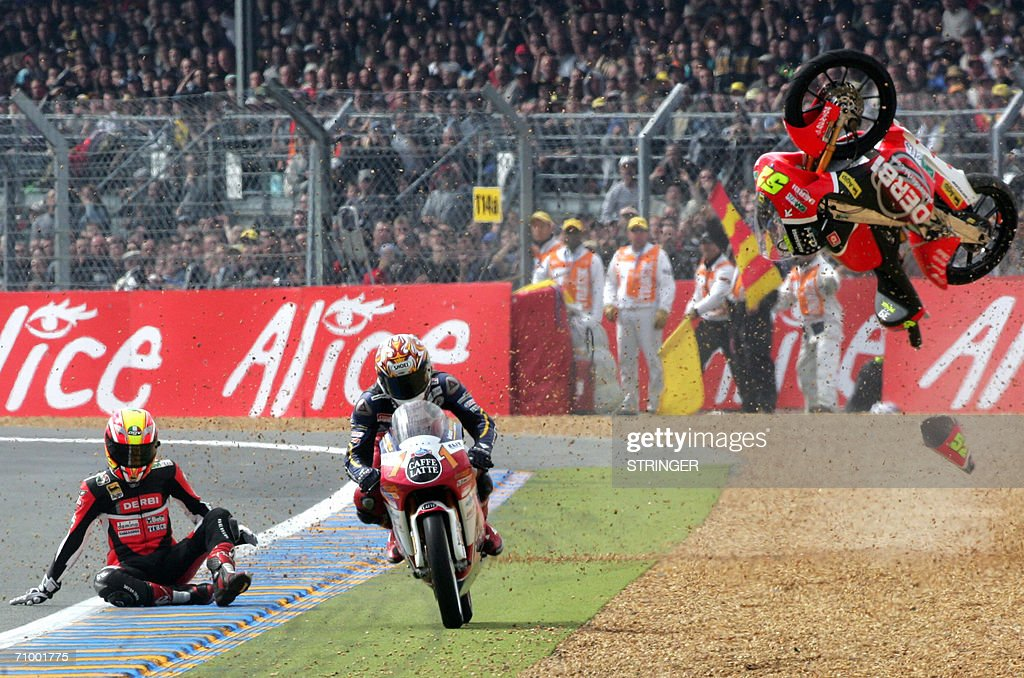 Swiss Thomas Luthi (C) rides his Honda as Czech Lukas Pesek falls down during the 125cc race during the French 125cc Grand Prix , 21 May 2006 at the Le Mans racetrack, western France.