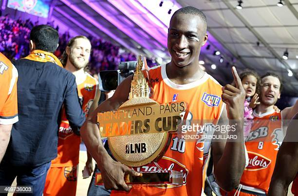 Le Mans' player Pape Sy holds a trophy as he celebrates after winning the Leaders Cup/ LNB 2014 basketball tournament final match on February 16 2014...