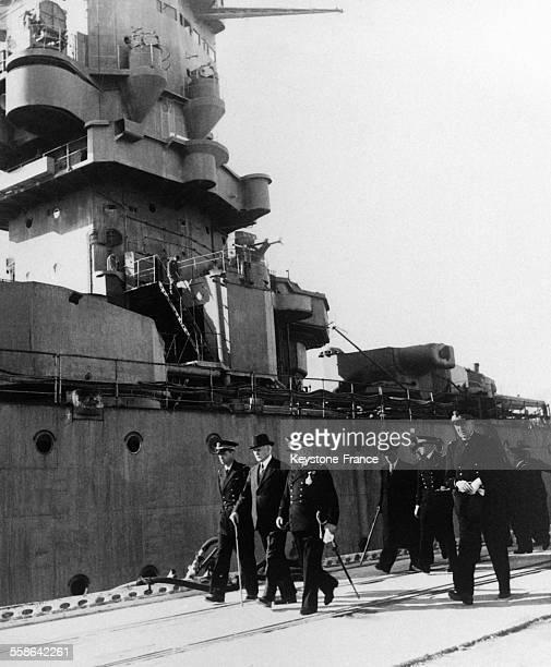 Le Maréchal Pétain chef de l'Etat accompagné de l'Amiral Darlan et du Commandant du 'Strasbourg' passe devant le majestueux bâtiment au cours d'une...