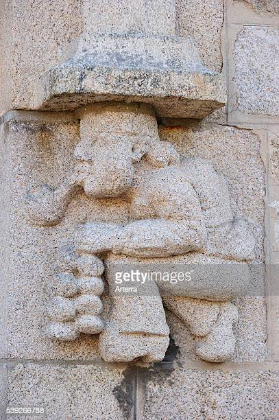 Le Marchand d'oignons / Johnny Onions stone figure with pipe and onions on house front at Roscoff Finistere Brittany France