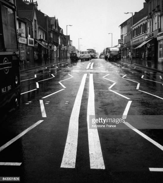 Le marquage au sol représentant des lignes blanches en zigzag dans la rue principale incite les automobilistes à ralentir le 28 octobre 1967 à...