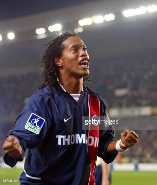 le milieu de terrain brésilien du PSG Ronaldinho auteur des premiers buts pour son équipe salue les supporteurs parisiens le 26 octobre 2002 au Parc...