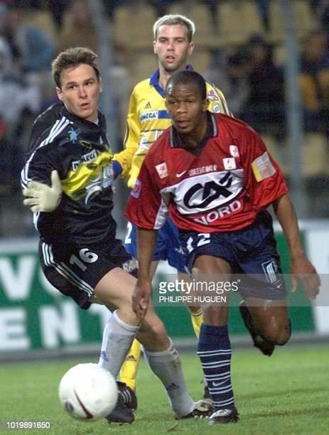 le milieu de terrain de Lille Kelton Agasson Bruno Cheyrou tente de passer le gardien de but de Gueugnon Richard Trivino le 15 avril 2000 au stade...