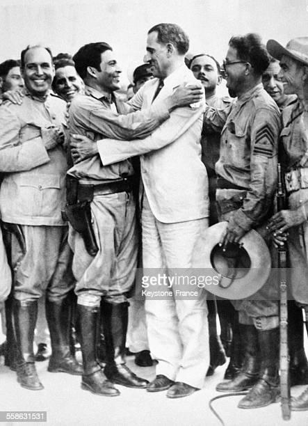 Le militaire Fulgencio Batista a gauche serrant dans ses bras le president cubain Ramon Grau San Martin au milieu d'un groupe de militaires a Cuba...