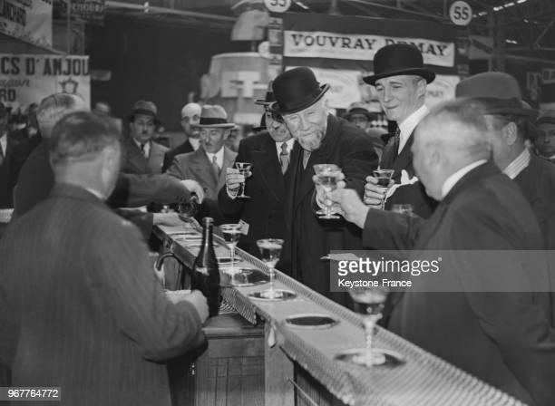 Le ministre de l'Agriculture Emile Cassez déguste un verre de vin à un stand de la Foire de Paris France le 22 mai 1935