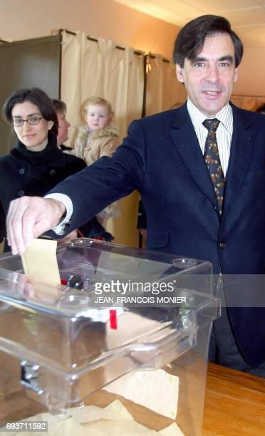 le ministre des Affaires sociales François Fillon tête de liste aux élections régionales dans les Pays de Loire met son bulletin dans l'urne sous les...