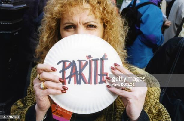 Le mot 'Parité' brandi par une femme participant à la manifestation devant le Sénat réclamant la parité en politique le 26 janvier 1999 à Paris France