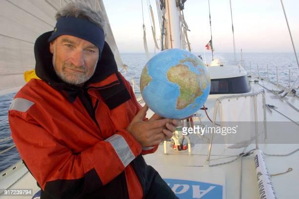 Le navigateur JeanLuc Van Den Heede pose avec un globe terrestre sur son bateau à l'aube du 06 octobre 2002 au large des côtes bretonnes Le marin...