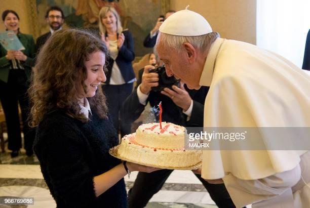 Le pape François souffle une bougie posée sur un gateau offert par une jeune fille de l'Action Catholique Italienne le jour anniversaire de ses 79...
