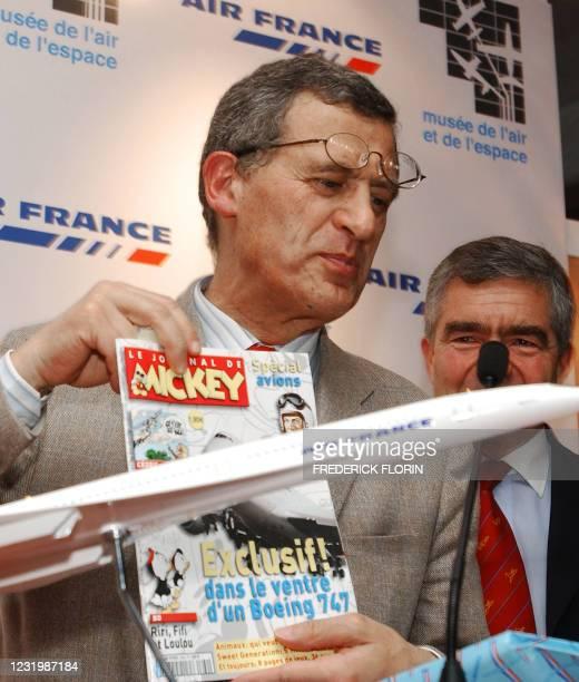 Le PDG d'Air France Jean Cyril Spinetta montre un exemplaire du journal de Mickey que vient de lui remettre le général Marc Alban , directeur du...
