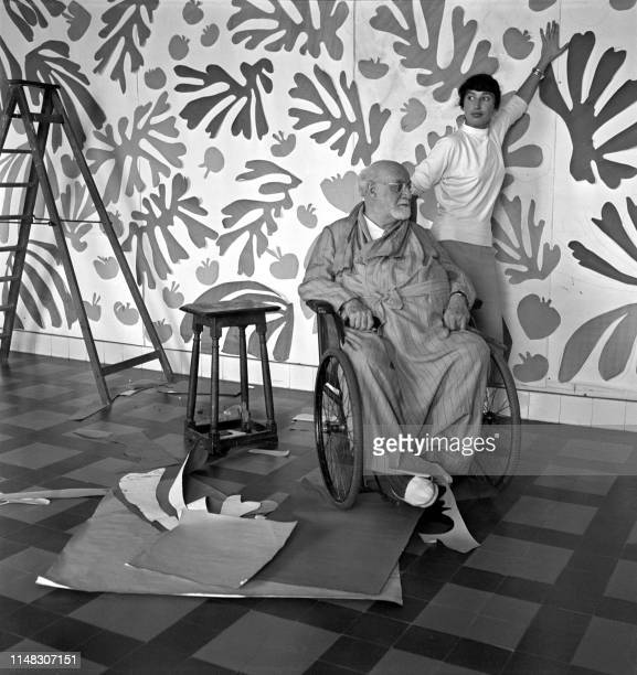 Le peintre et sculpteur français Henri Matisse pose dans son atelier au Régina, à Nice, en 1952, devant l'oeuvre monumentale en papiers gouachés...