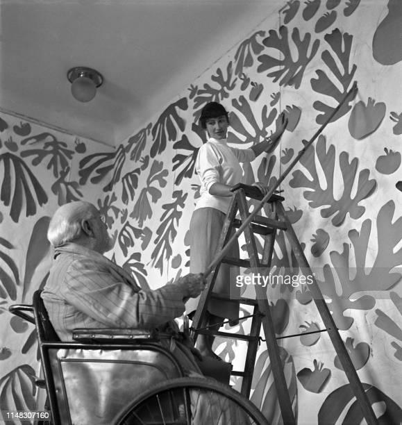 Le peintre et sculpteur français Henri Matisse travaille dans son atelier au Régina, à Nice, en 1952, devant l'oeuvre monumentale en papiers gouachés...