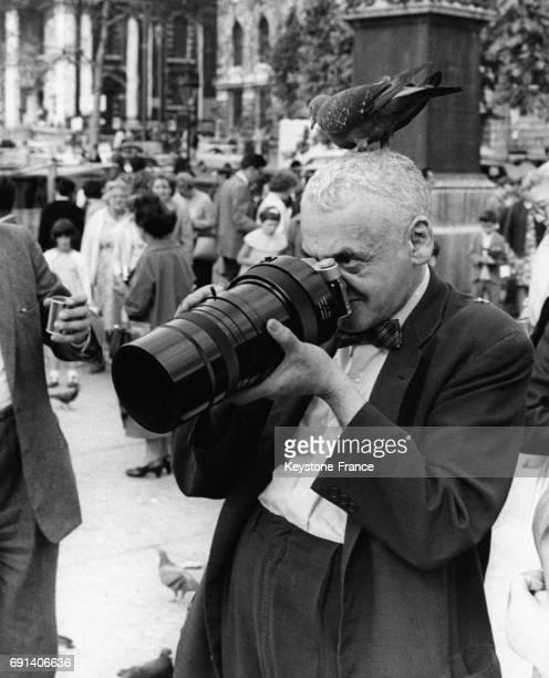 Le photographe américain Weegee photographiant au zoom avec son appareil photo russe sur Trafalgar Square un pigeon posé sur la tête à Londres...
