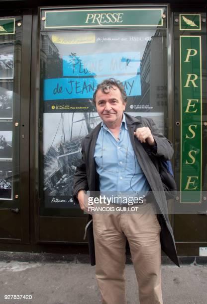 Le photographe de l'agence Magnum Jean Gaumy pose le 06 juillet 2007 à Paris devant un kiosque de presse sur lequel est exposée une de ses...