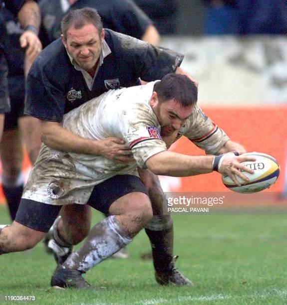 le pilier du Stade Toulousain Pascal Gentil tente de marquer un essai le 18 décembre 1999 à Toulouse malgré l'opposition d'un joueur Italien du Simac...