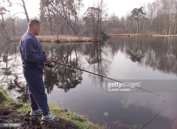 le pilier international Christian Califano pêche dans l'étang du château de Clairefontaine le 17 mars 2000 lors d'un stage d'entraînement du XV de...