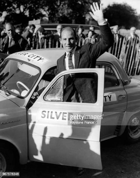 Le pilote anglais Stirling Moss fait un signe de la main à la foule avant de monter en voiture à Marble Arch pour s'envoler pour le Prix Louis...