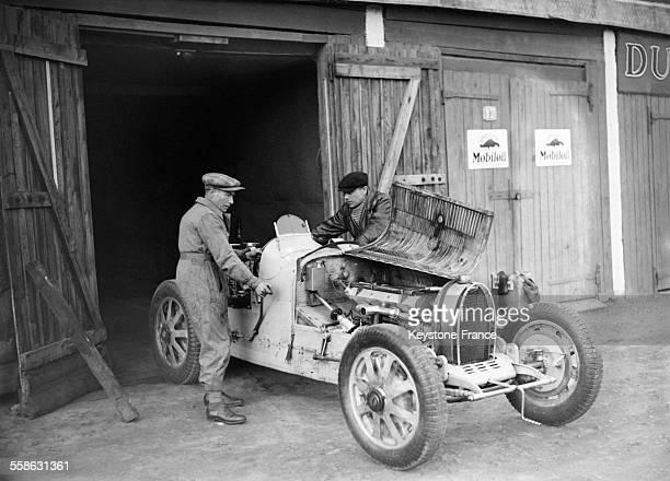 Le pilote automobile Robert Benoist travaillant sur sa Bugatti avec son mecanicien a Montlhery France