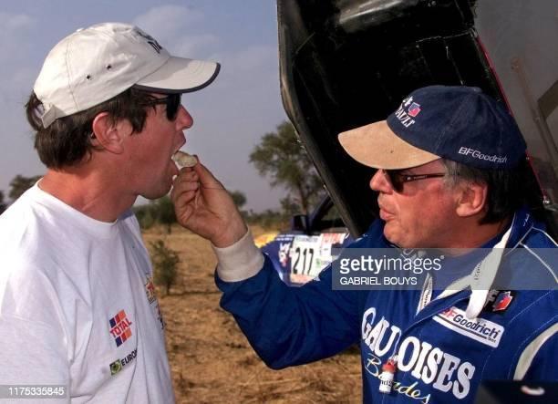 le pilote français JeanLouis Schlesser donne du pain à Hubert Auriol le 10 janvier après sa victoire dans la spéciale Bobo Dioulasso Mopti 9e étape...