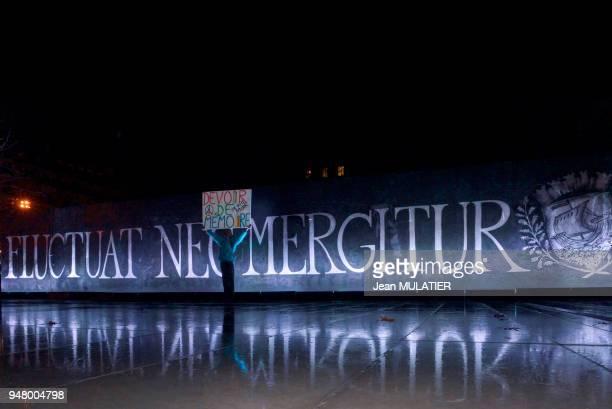 Le 'poète activiste' Voltuan portant une pancarte 'Devoir de mémoire' devant la banderole avec l'inscription 'Fluctuat nec mergitur' signifiant 'Il...
