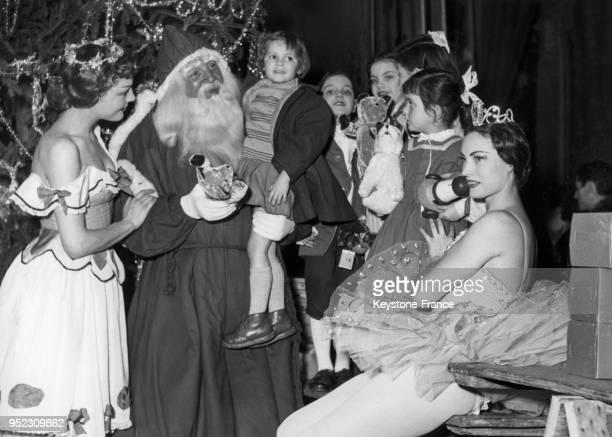 Le Père Noël entouré des danseuses du ballet 'CasseNoisettes' distribue des jouets aux enfants lors de l'arbre de Noël des théâtres nationaux à...