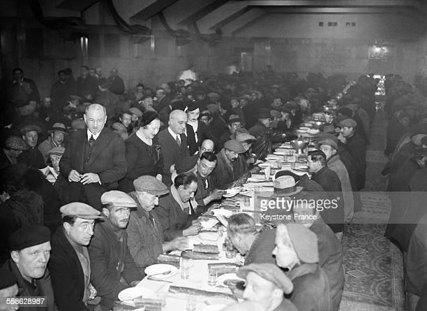 Le prefet de police Jean Chiappe et son epouse au milieu de clochards parisiens auxquels la Prefecture de Police a offert un repas de Noel a Paris...