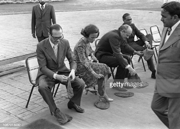 Le Premier ministre français Jacques Chirac et sa femme Bernadette enfilent des chaussons de protection en janvier 1976 lors d'un voyage officiel en...
