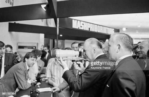Le premier ministre Georges Pompidou examinant un appareil photographique sur le stand soviétique à la Foire de Paris à Paris en France le 20 mai 1967