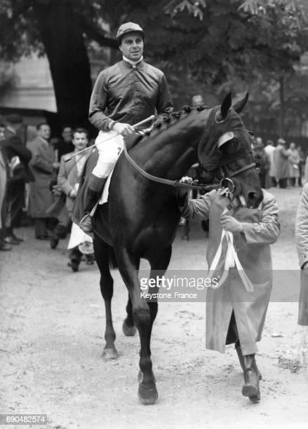 Le Prince Ali Khan montant le cheval 'Nearque 11' après une course à l'hippodrome de Longchamp à Paris France en 1949