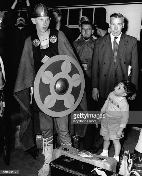 Le Prince Chistian de Danemark portant le déguisement de Viking à son arrivée à la gare de Victoria sous le regard étonné d'un petit garçon à Londres...