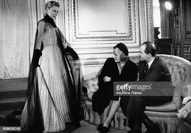 Le Prince Otto de Habsbourg et sa fiancee la princesse Regina de SaxeMeiningen chez le grand couturier Jean Desses regardent un mannequin qui leur...