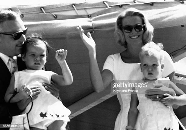 Le Prince Rainier tenant dans ses bras sa fille Caroline et sa femme la Princesse Grace tenant son fils le Prince Albert saluent lors de leur séjour...