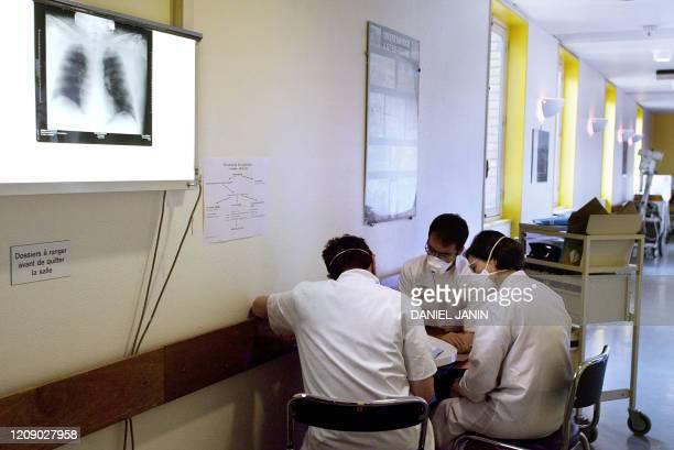 le professeur JeanLouis Vilde chef du service des maladies infectieuses et tropicales de l'hôpital Bichat à Paris examine le 03 avril 2003 avec deux...