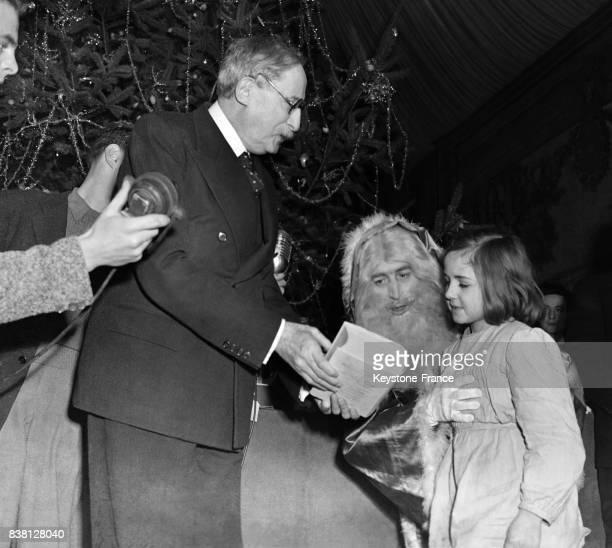 Le président Blum assisté du Père Noël distribue les cadeaux devant l'arbre de Noël à Paris France en décembre 1946