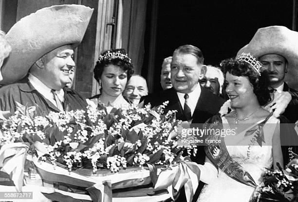 Le président de la république française René Coty au centre entouré de la Reine du muguet à gauche et de la Reine des Halles à droite pour la...