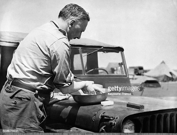 Le Président de la République française se lave les mains avec du savon dans un bac posé sur le capot d'une jeep à Dien Bien Phu circa 1950 au Vietnam