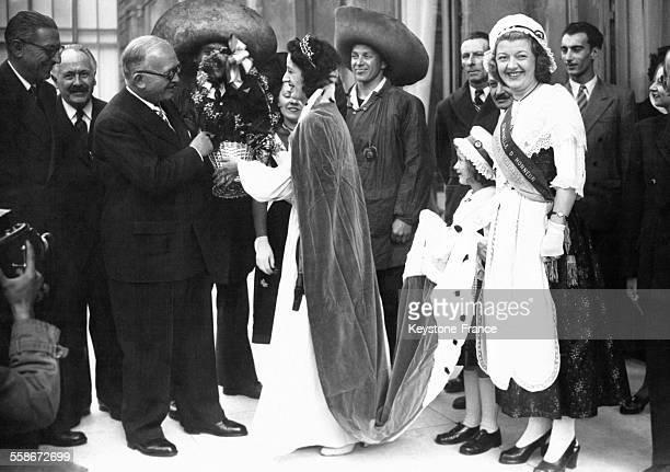 Le Président de la République française Vincent Auriol reçoit une corbeille de muguet des mains de la Reine du 1er arrondissement comme le veut la...