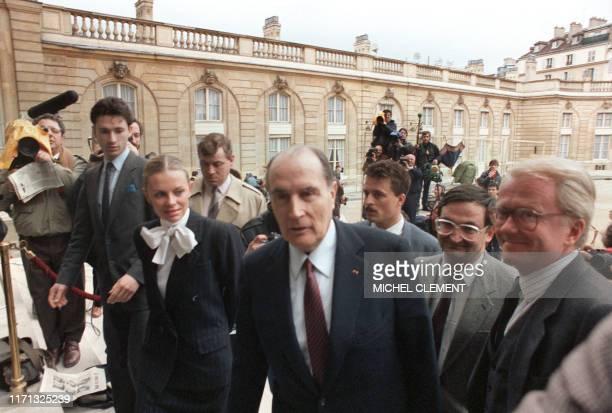 Le président de la République François Mitterrand entouré d'Elisabeth Guigou et Jacques Attali est assailli par les journalistes à son arrivée dans...